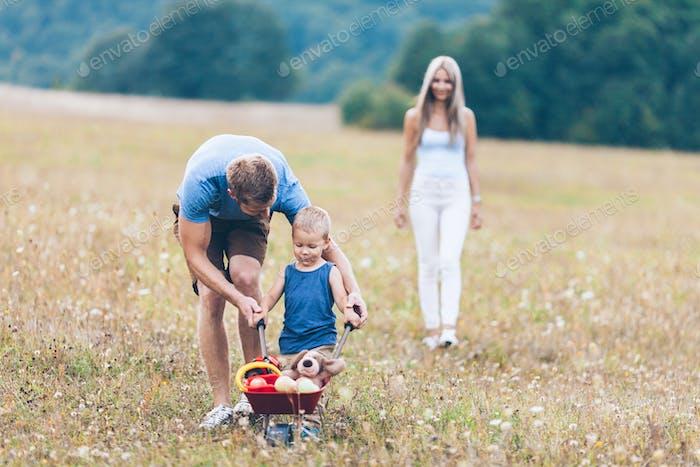 Criança com seus pais empurrando um carrinho de baleia ao ar livre
