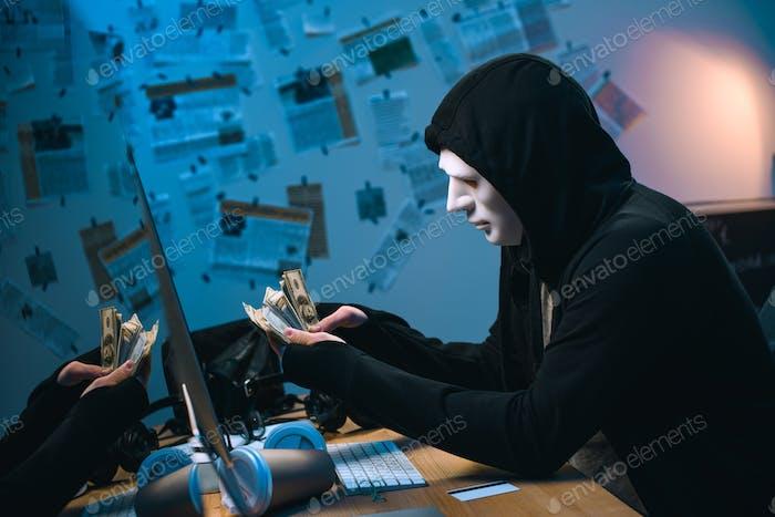 vista lateral del hacker encapuchado en máscara contando dinero robado en su lugar de trabajo