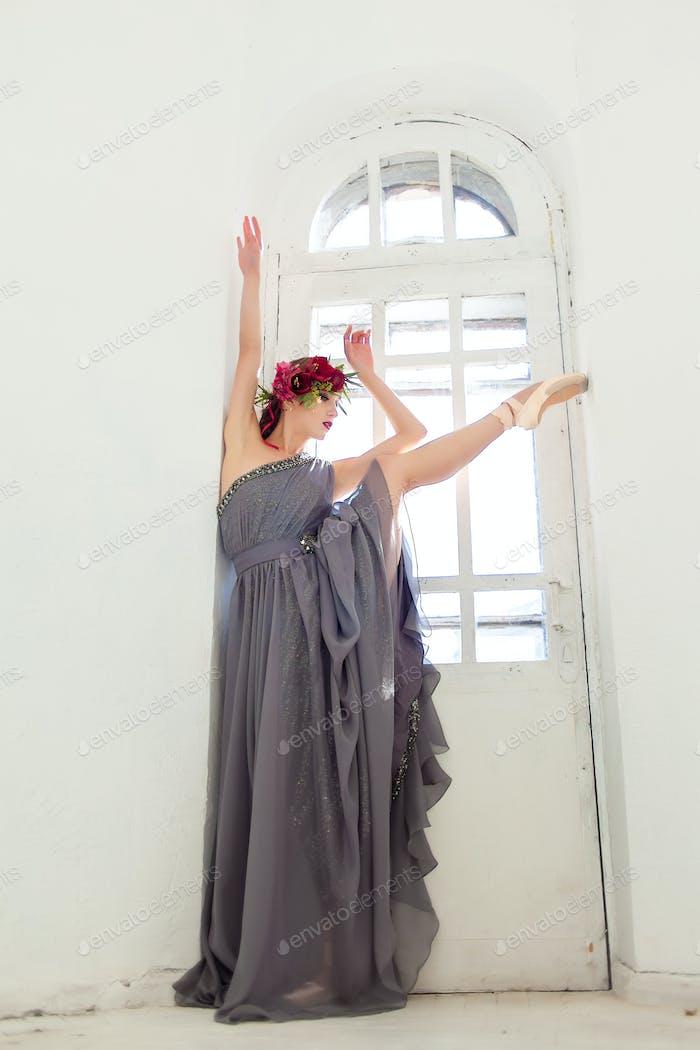 Die schöne Ballerina posiert in langen grauen Kleid