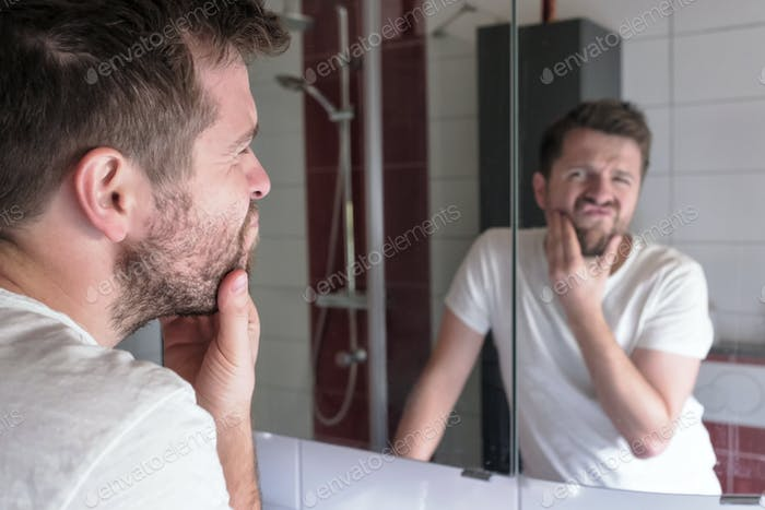 Mann überprüfen Zustand seiner Haut in Spiegelreflexion am Bad