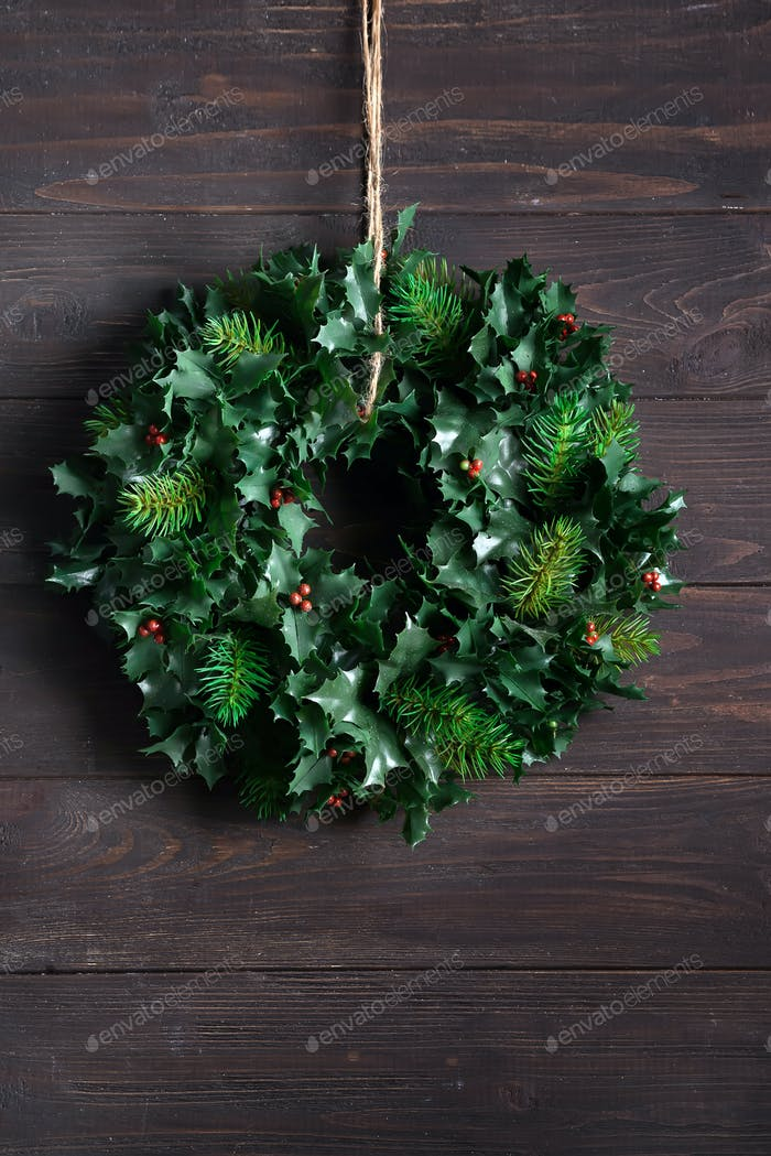 Christmas decoration wreath of green leaves and berries holly ilex plant isolated on dark wooden