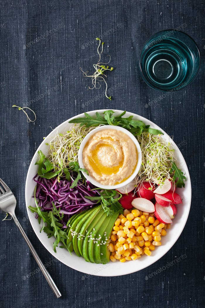 vegan avocado sweet corn lunch bowl with hummus, red cabbage, radish and sprouts