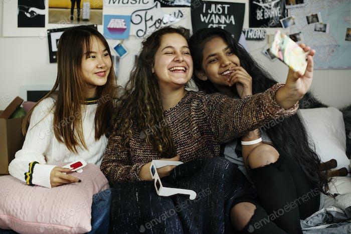 Teenager-Mädchen mit einem Smartphone, um ein Selfie in einem Schlafzimmer Hangout und Freundschaftskonzept zu nehmen