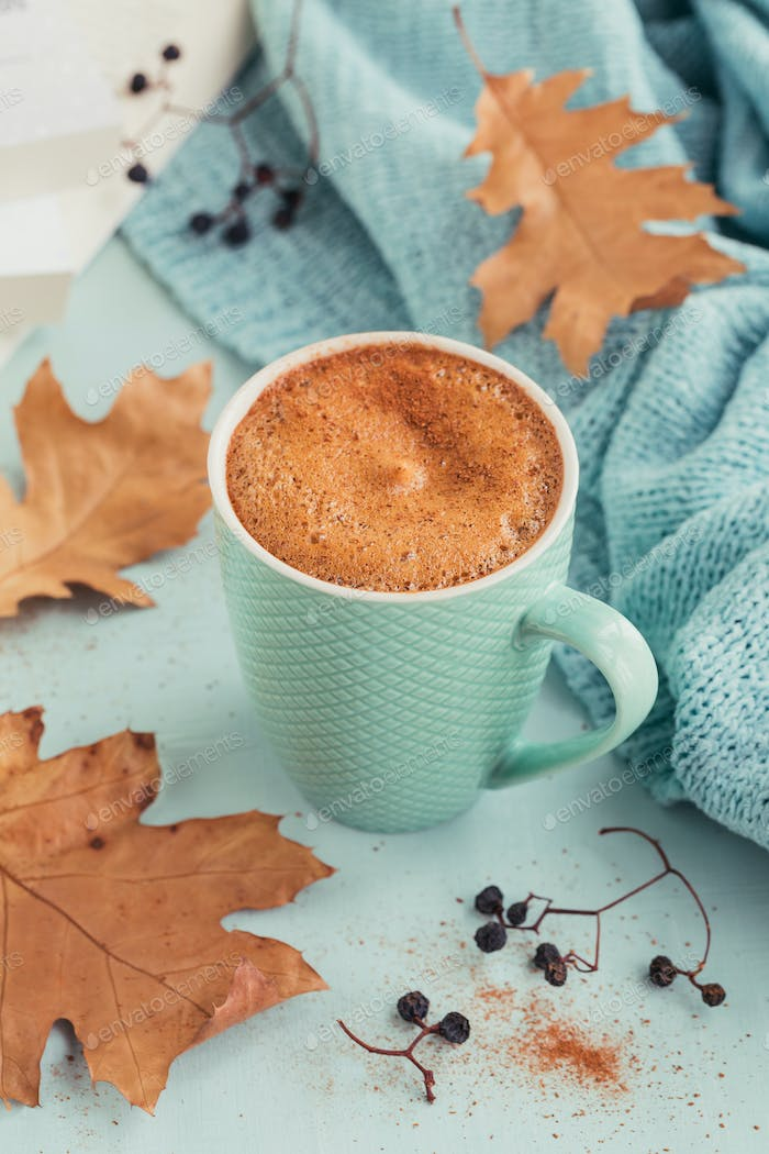 Blue cup of coffee with autumnal dry leaves and dry berries