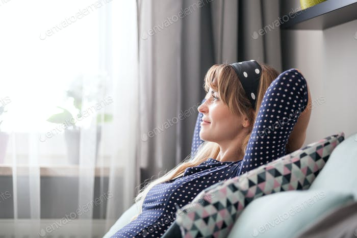 Happy young woman sitting on sofa relaxing at home
