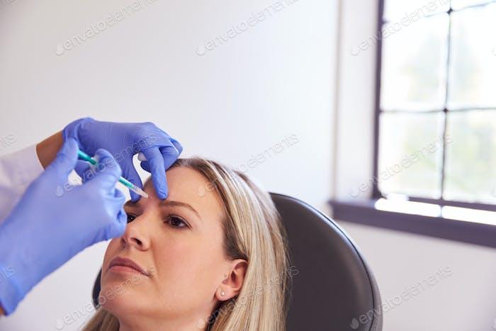Frau sitzend in Stuhl Sein Geben Botox Injektion in Stirn Von Weiblichen Arzt