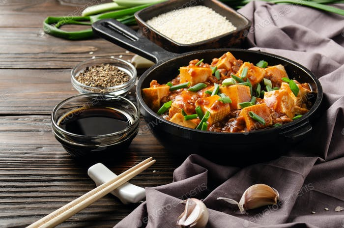 Mapo tofu in cast iron skillet with pork chopped chives soy sauce sichuan pepper