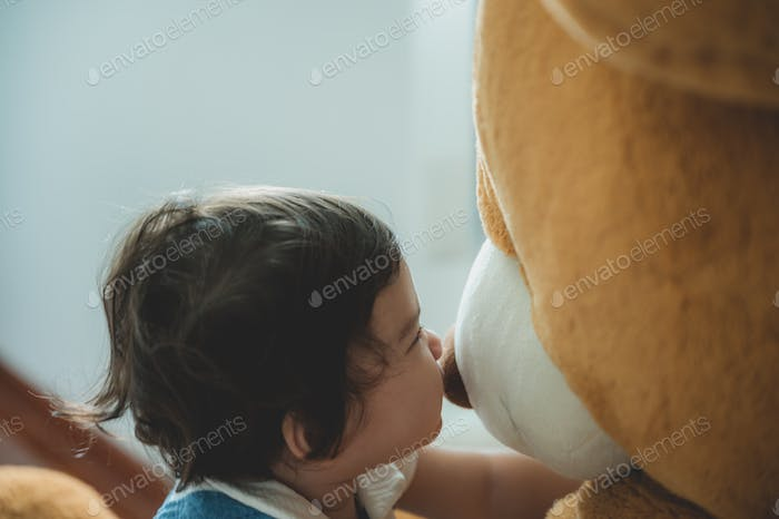 Adorable baby playing with the big bear doll with the happy young family