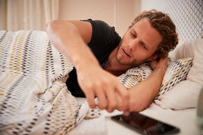 Millennial white man waking up in bad and reaching for smartphone, close up