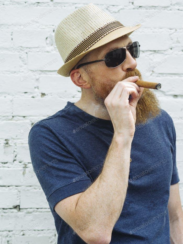 Bärtiger Mann, der eine Zigarre raucht
