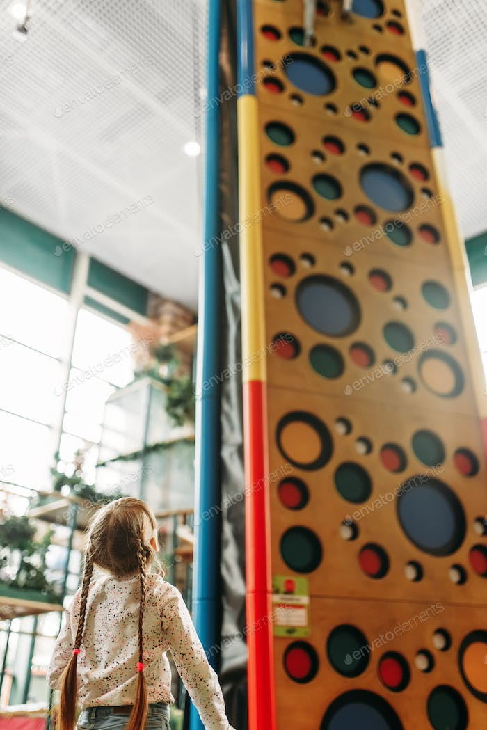 Little girl looks on climbing wall, game center