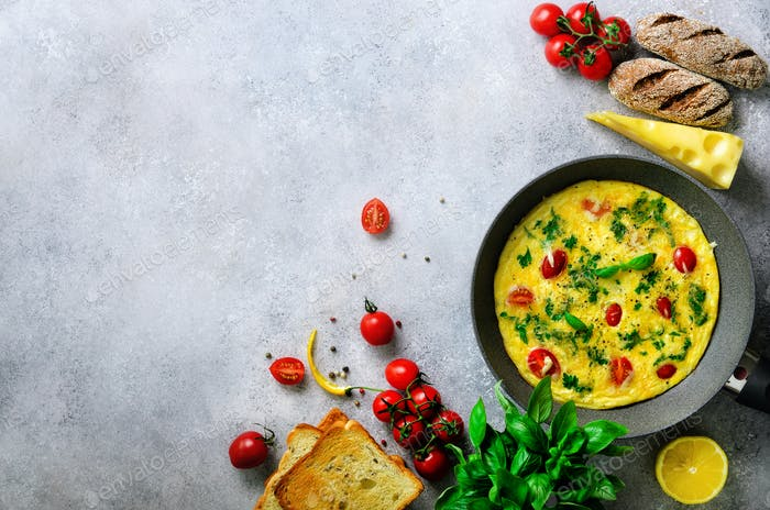 Homemade classic omelet with cherry tomatoes, cheese and herbs on grey concrete background. Frittata