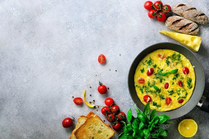 Hausgemachtes klassisches Omelett mit Kirschtomaten, Käse und Kräutern auf grauem Betongrund. Frittata