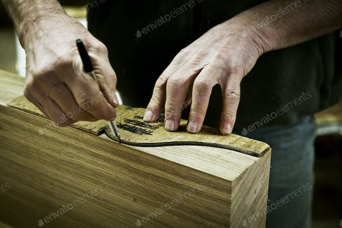 A man working in a furniture maker's workshop drawing around a shape on wood.