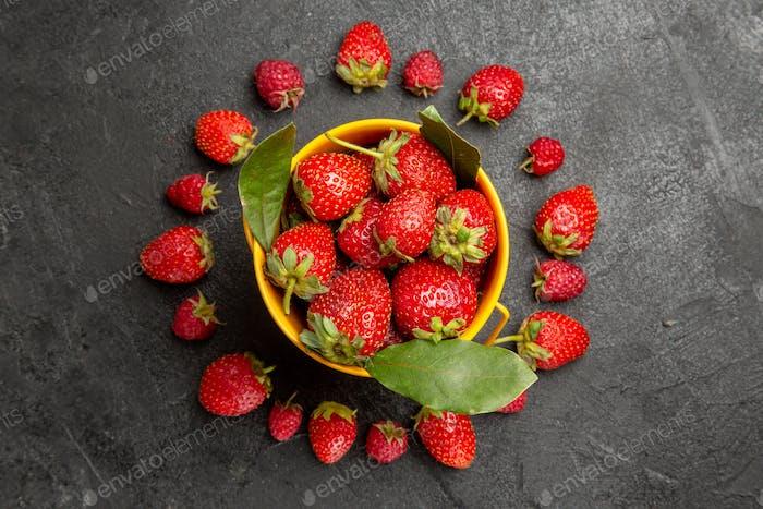 Draufsicht der frischen roten Erdbeeren, die auf dunklem Hintergrund gesäumt sind