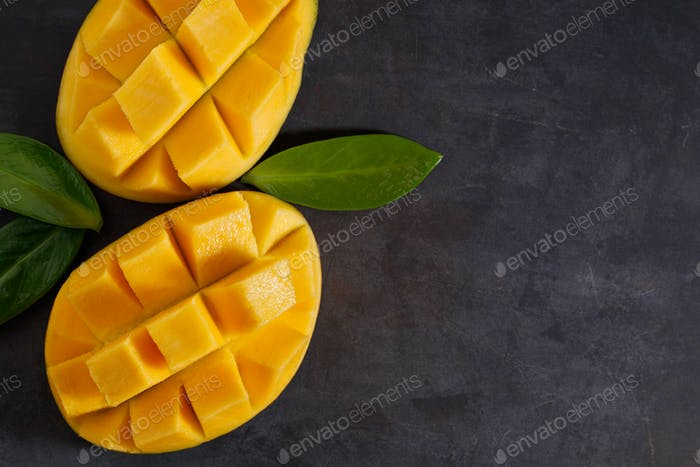 The two halves of ripe mango on the black textured table. View from above. Copy space.
