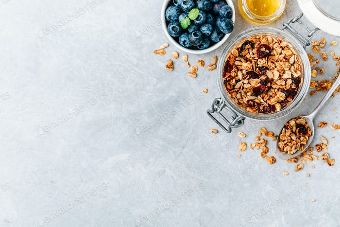 Gesundes Frühstück Müsli mit frischer Heidelbeere und Honig auf grauem Stein Hintergrund