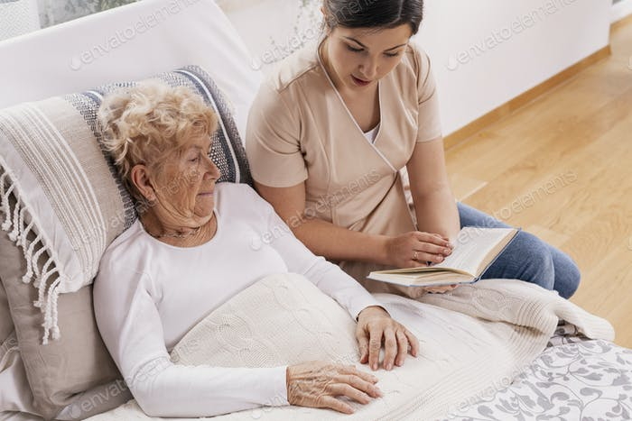 Helpful female volunteer reads a book to an elderly woman lying in a bed