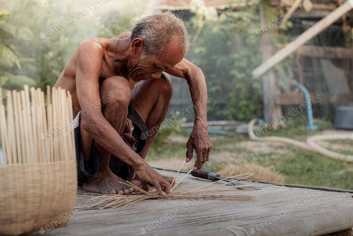 Old man are weaving of Thailand