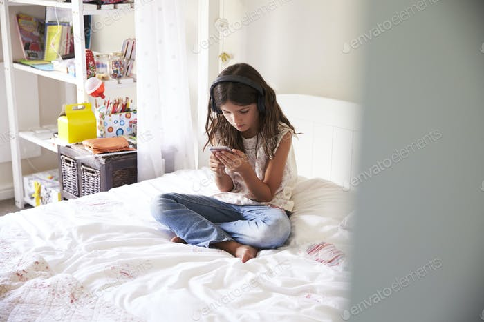 Girl Sitting On Bed Listening To Music On Headphones