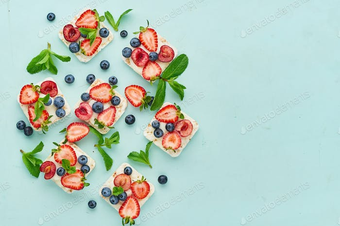 Rise crispbread with berries and fruits colorful concept on turquoise aquamarine background