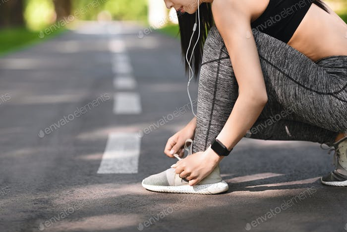 Sporty girl tying shoes laces before running, getting ready for jogging outdoors
