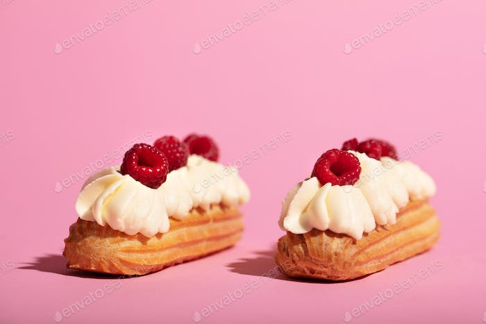 Two colorful eclairs laying on pink background.