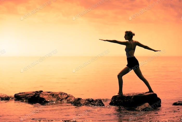 Junge Frau macht die Krieger-Yoga-Position vor dem Ozea