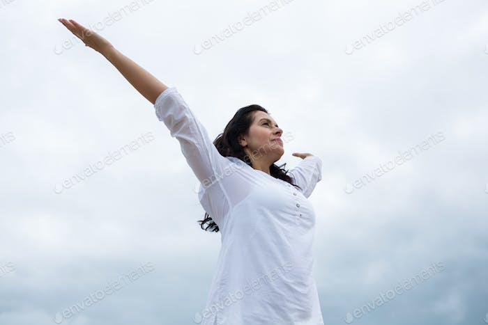 Happy woman standing with arms outstretched