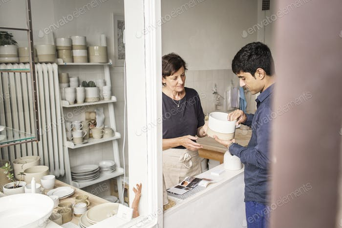 Potter showing product to customer