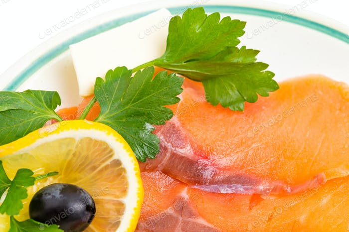 Delicious sliced salmon with lemon and olive.