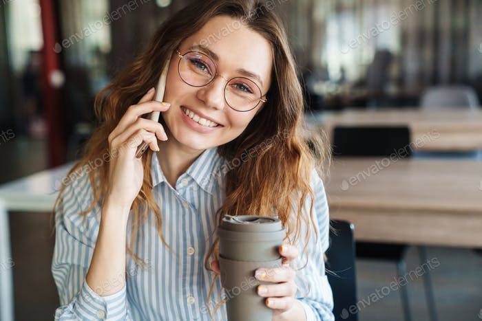Image of happy young woman talking on cellphone and drinking coffee