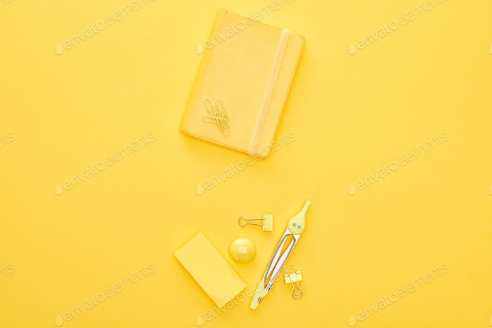 Top View of Yellow Notepad And Stationery on Same Background
