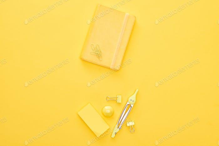 Draufsicht von gelben Notizblock und Briefpapier auf demselben Hintergrund