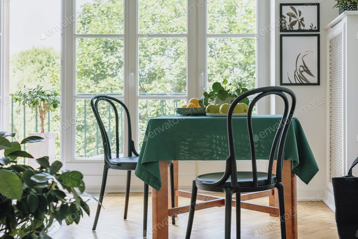 Two black chairs standing by dining table with apples, lemons, f