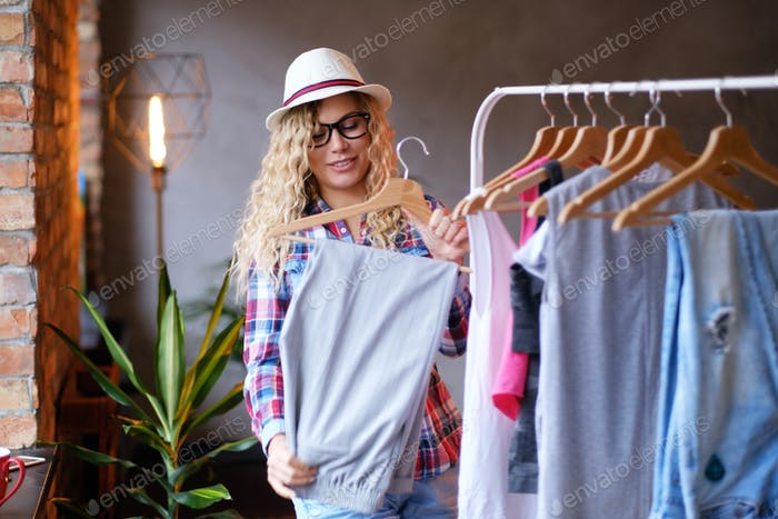 Happy young woman in hat and glasses  is tidy up in her wardrobe for summer at modern loft.