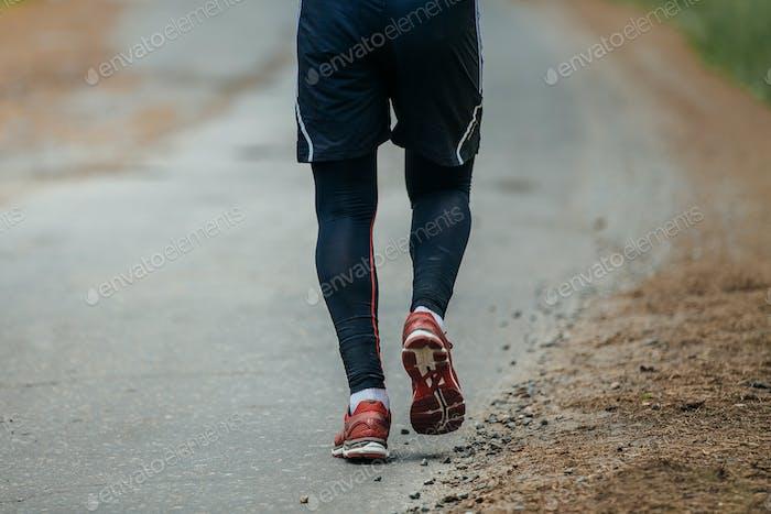 Mann läuft auf Straße in Wald