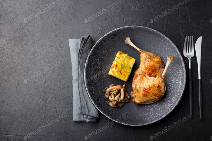 Duck Legs Confit with Potato Gratin and Mushroom Sauce. Restaurant Serving. Copy Space. Top view.