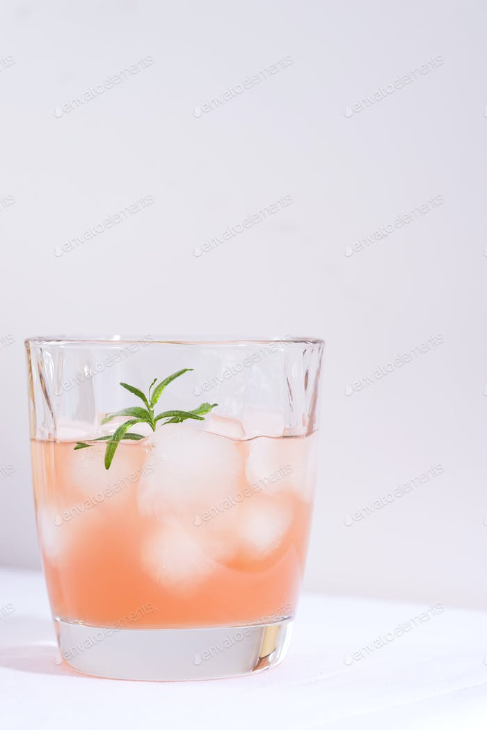 Pink cocktail with rosemary and ice in glass on a white tablecloth on the table
