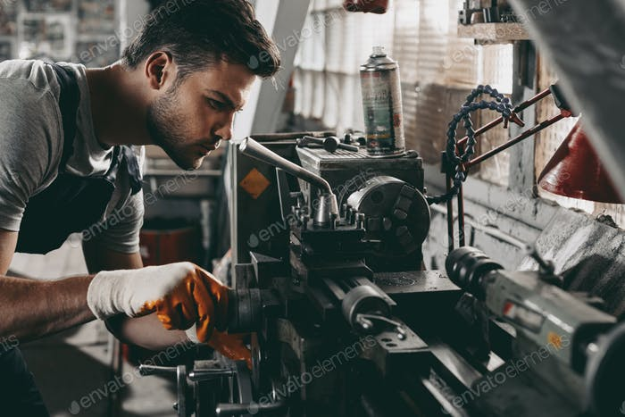young handsome mechanic working in workshop