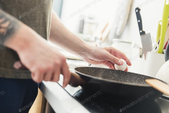 Man preparing fried eggs in the kitchen