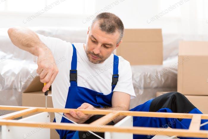 Professional Carpenter Fixing Wooden Shelf Assembling Furniture In Flat