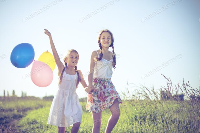 Happy little children playing in the field at the day time.