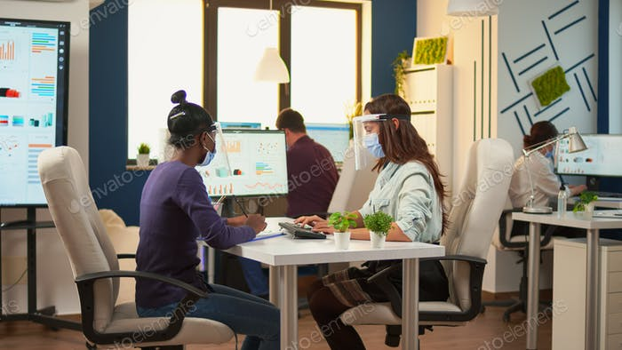 Multi ethnic employees with visor sitting at desk analysing statistics