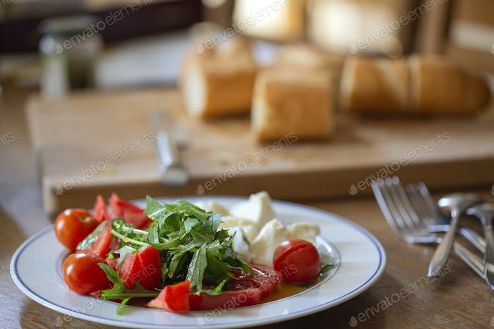 Cherry tomatoes with arugula leaves and pieces of mozarella cheese