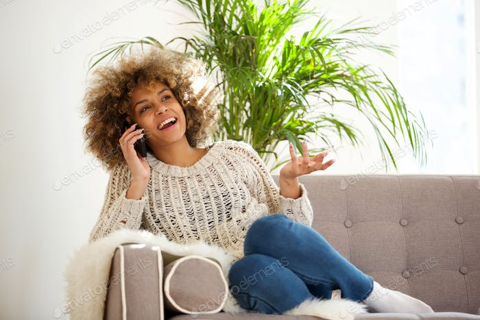 happy young black woman talking on mobile phone at home