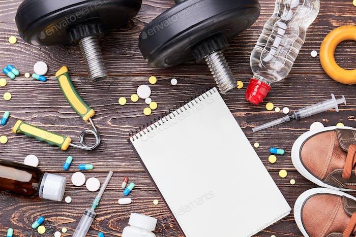 Cuaderno vacío, jeringas, pastillas, pesas