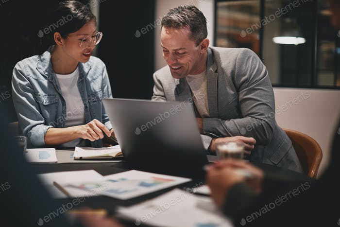 Smiling businesspeople going over paperwork during an office meeting