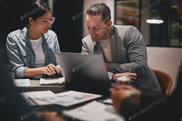 Улыбающиеся бизнесмены переходят на бумажную работу во время офисной встречи