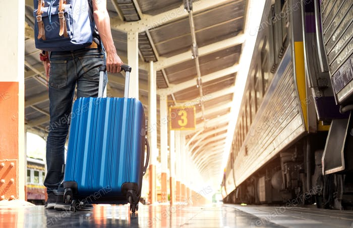 Asian tourist is dragging a blue suitcase with wheels on the tra
